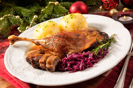 christmas dish: Crusty goose leg with braised red cabbage and dumplings on Christmas decorated table Stock Photo