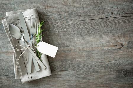 decoracion mesas: Cubiertos con una ramita de romero y etiqueta vacía en el fondo de madera rústica Foto de archivo