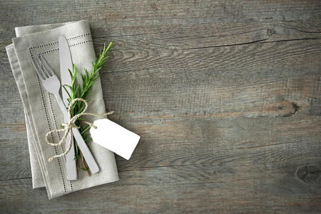 grunge cutlery: Silverware with a twig of rosemary and empty tag on rustic wooden background