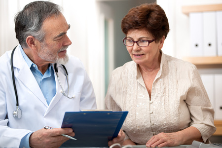 dos personas platicando: Doctor que habla con su paciente mayor femenino en la oficina