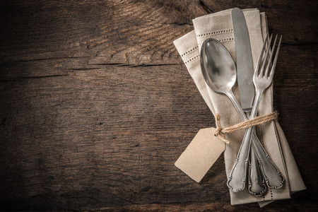 Vintage silverware with an empty tag on rustic wooden background 免版税图像