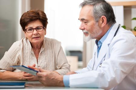 consulta médica: Doctor que habla con su paciente mayor femenino en la oficina