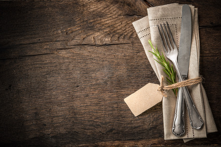 Vintage silverware with a twig of rosemary and empty tag on rustic wooden background