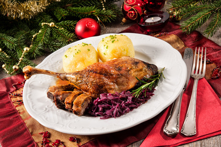 red braised: Crusty goose leg with braised red cabbage and dumplings on Christmas decorated table Stock Photo
