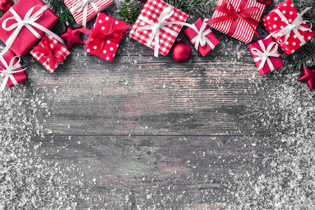 Christmas background with decorations and gift boxes on wooden board