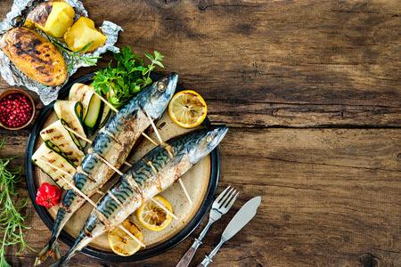 Pescados de la caballa a la plancha con papas al horno en mesa de madera Foto de archivo - 43659778