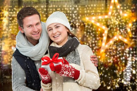holiday lighting: Young man giving his girlfriend Christmas present in front of holiday lighting