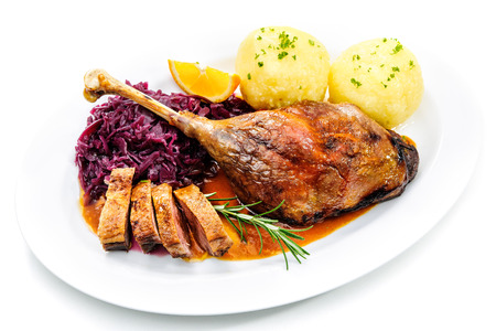 Crusty goose leg with braised red cabbage and dumplings isolated on white