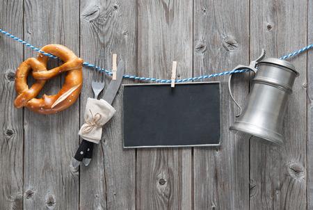 メッセージ、ビアマグ、木製基板に対して物干し用ロープにぶら下がっているプレッツェル。オクトーバーフェストの背景 写真素材