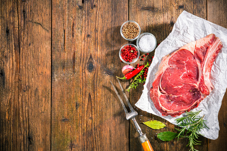 Raw fresh meat rib eye steak and seasoning on dark background Zdjęcie Seryjne - 43659789
