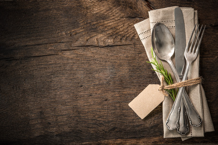 dining set: Vintage silverware with a twig of rosemary and empty tag on rustic wooden background
