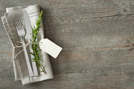 setting: Silverware with a twig of rosemary and empty tag on rustic wooden background