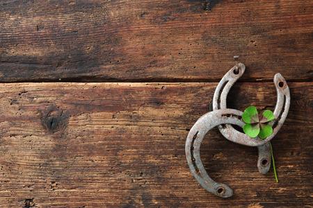 St. Patricks día, los amuletos de la suerte. Dos herraduras con un trébol de cuatro hojas sobre tabla de madera Foto de archivo - 44129896