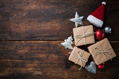 christmas santa: Christmas Santa Claus hat with gift boxes and decoration over grunge wooden background Stock Photo