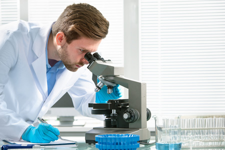 experimento: Científico que mira a través de un microscopio en un laboratorio