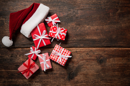 Christmas Santa Claus hat with gift boxes and decoration over grunge wooden background Stock Photo