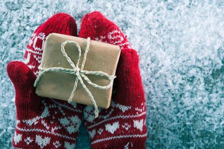 manos: Manos femeninas en los guantes de invierno con caja de regalo de navidad Foto de archivo