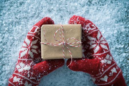 cajas navide�as: Manos femeninas en los guantes de invierno con caja de regalo de navidad Foto de archivo