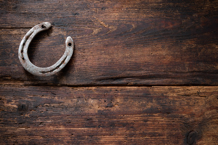 Old rusty horseshoe on vintage wooden board Archivio Fotografico