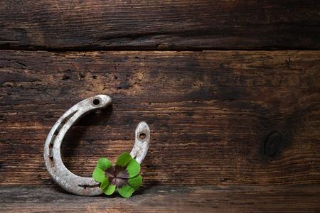 buena suerte: St. Patricks día, los amuletos de la suerte. Trébol de cuatro hojas y una herradura sobre tabla de madera Foto de archivo