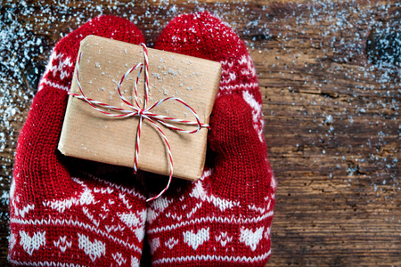 christmas gift box: Female hands in winter gloves with christmas gift box
