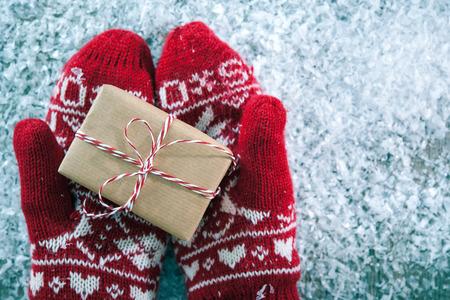 neige noel: Mains des femmes dans les gants d'hiver avec bo�te de cadeau de No�l Banque d'images