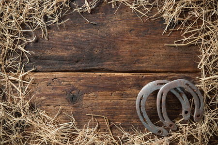 Two old rusty horseshoes surrounded by straw on vintage wooden board 스톡 콘텐츠