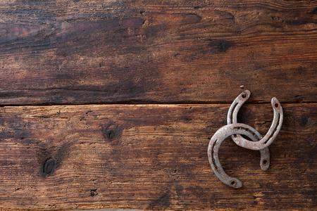 vaquero: Dos viejas oxidadas herraduras sobre tabla de madera de la vendimia