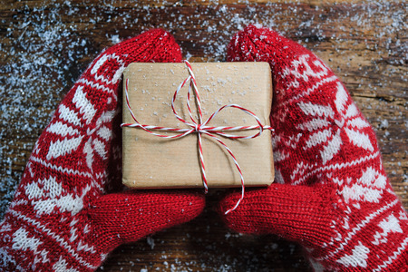 female christmas: Female hands in winter gloves with christmas gift box