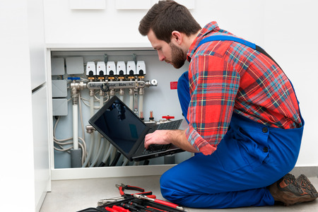 servicing: Technician servicing the underfloor heating