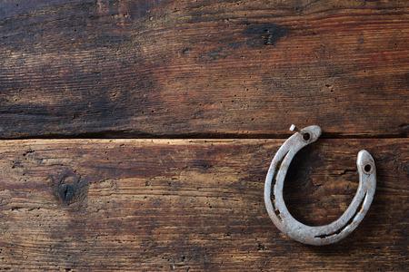 ビンテージ木製基板上の古い錆びた蹄鉄