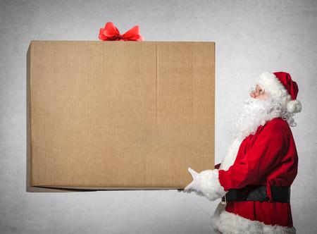De Kerstman houdt een grote gift box met copyspace voor uw tekst