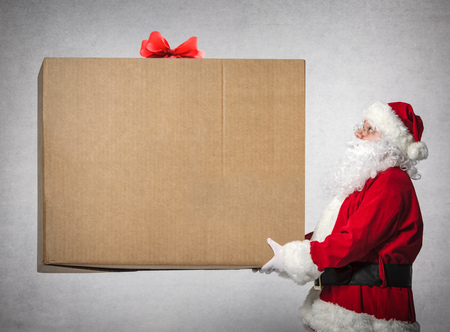 Santa Claus holds a big gift box with copyspace for your text