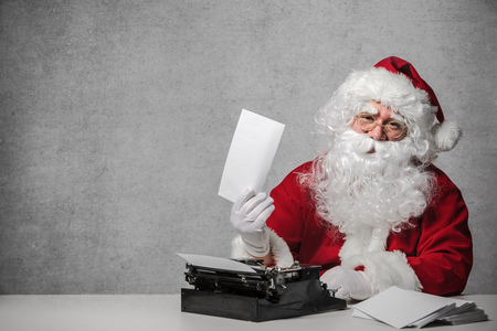 red wall: Santa Claus typing a letter on an old typewriter Stock Photo