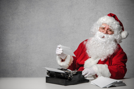 Santa Claus typing a letter on an old typewriter 스톡 콘텐츠