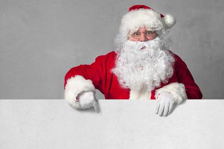 santa claus: Pap� Noel que se�ala en la muestra en blanco Foto de archivo