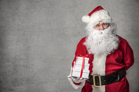 claus: Santa Claus with a small stack of gifts Stock Photo
