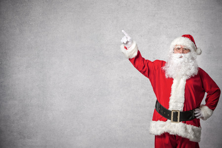 Santa Claus pointing with a finger on a white wall