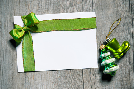 Holidays gift card with green bow on wooden background