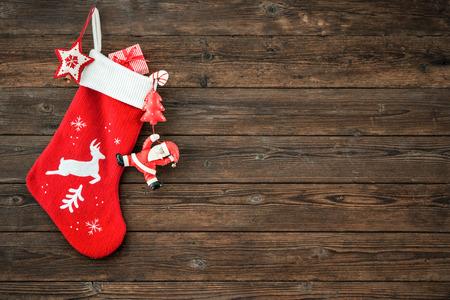 소박한 나무 배경 위에 매달려 크리스마스 장식의 스타킹과 장난감