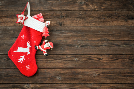 Christmas decoration stocking and toys hanging over rustic wooden background Stockfoto