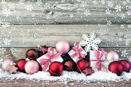 Christmas composition with colorful balls and gift boxes on snow Foto de archivo