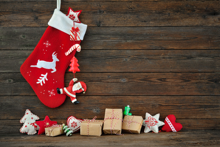 juguete: Decoraci�n de la media y los juguetes de Navidad colgando sobre fondo de madera r�stica