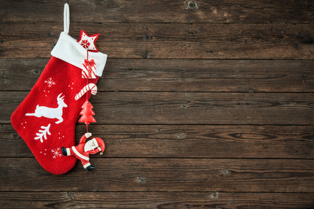 Christmas decoration stocking and toys hanging over rustic wooden background Foto de archivo