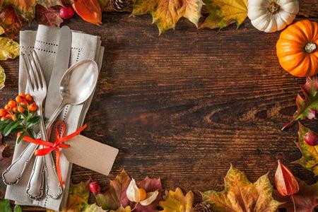accion de gracias: Acci�n de Gracias ajuste con cubiertos y arreglo de coloridas hojas de oto�o lugar oto�o Foto de archivo