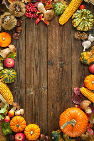cuerno de la abundancia: Recoger o acción de gracias de fondo con frutos otoñales y calabazas en una mesa de madera rústica