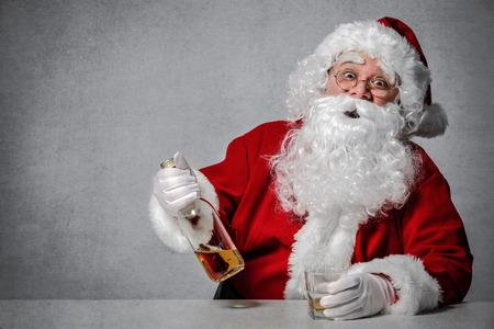Weihnachtsmann mit einer Flasche Whisky bei einem Drink und einer Rast