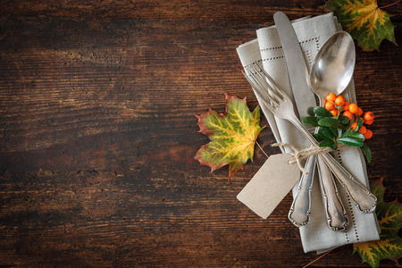 place card: Thanksgiving autumn place setting with cutlery and arrangement of colorful fall leaves Stock Photo
