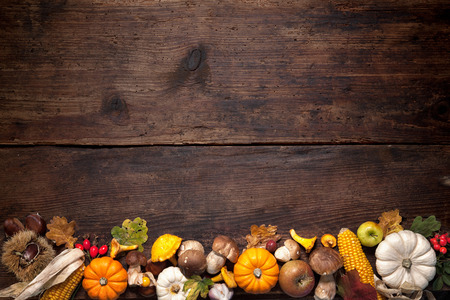 table decorations: Harvest or Thanksgiving background with autumnal fruits and gourds on a rustic wooden table