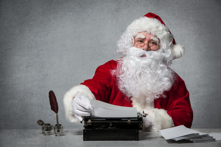 old man sitting: Santa Claus typing a letter on an old typewriter Stock Photo